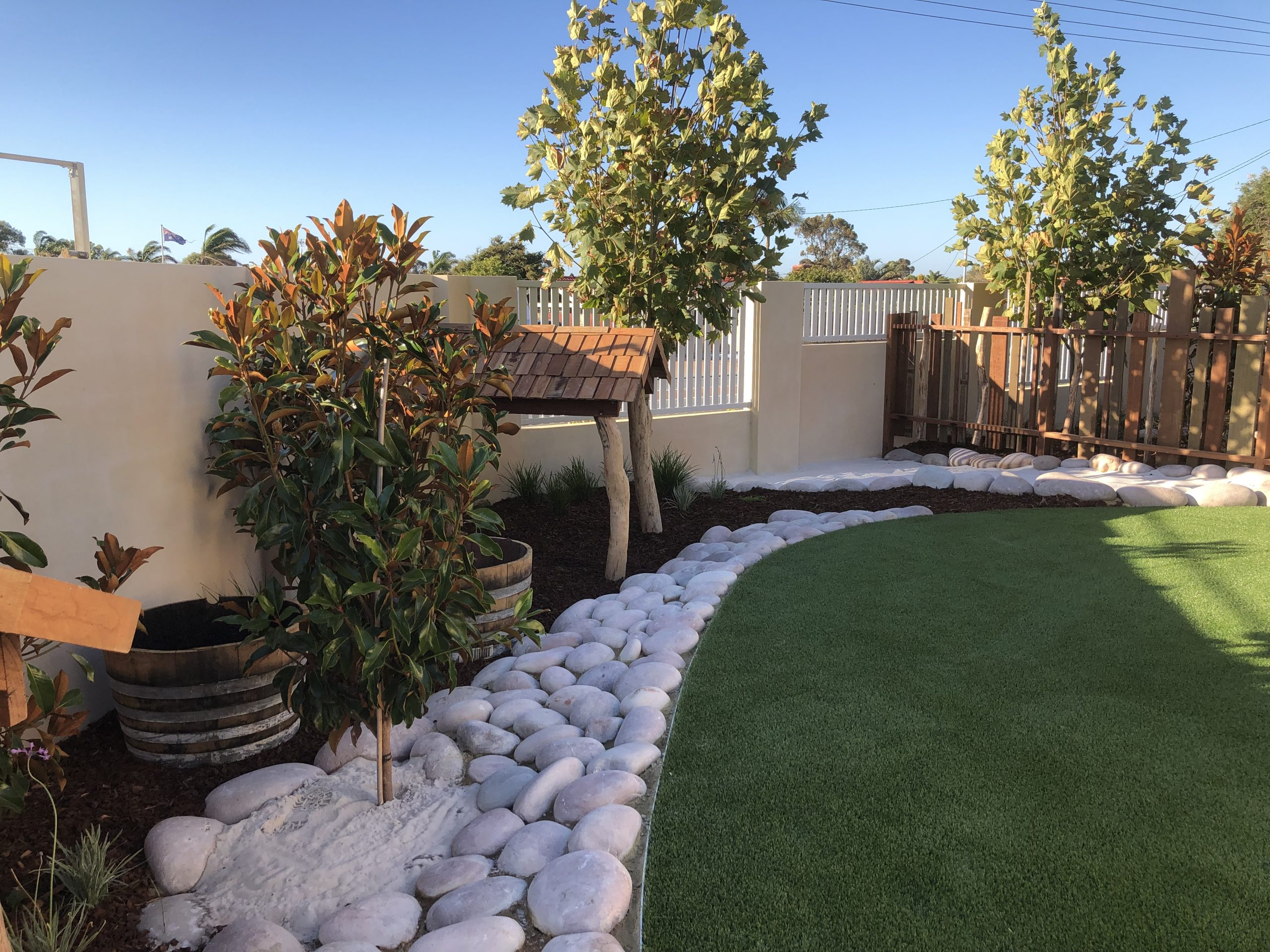 Clean grass carpet with large white stone pebbles.